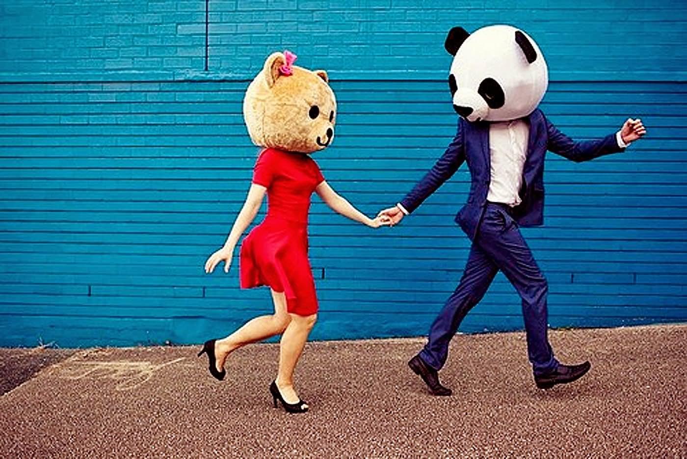 Imagen de dos personas andando, una vestida con un vestido rojo y la otra con un traje azul. Ambas llevan en la cabeza una cabeza de disfraz